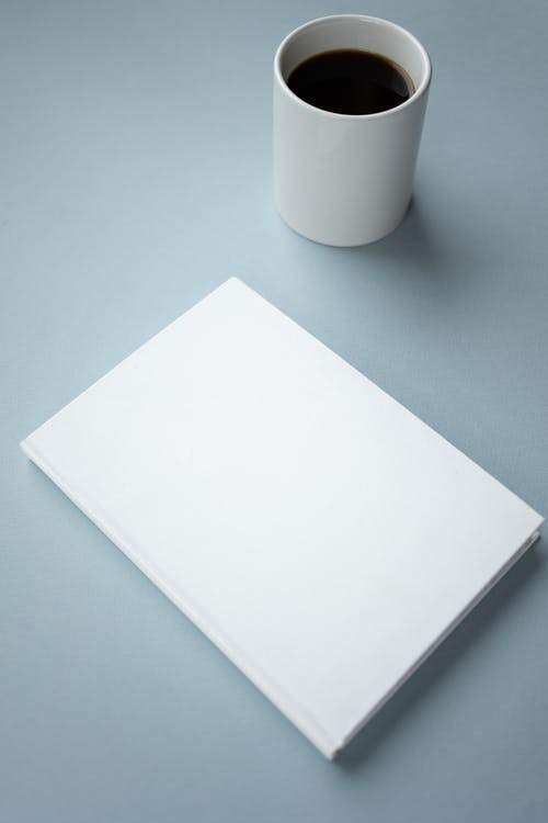 High angle of mockup of white hardcover of notebook placed near white ceramic cup of americano on table
