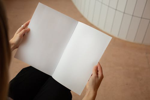 High angle of crop unrecognizable female looking on blank sheets of paper while sitting in light room
