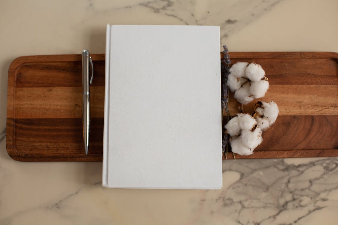 Overhead view of composition of empty hardcover book lying between metallic pen and soft cotton flowers on wooden tray with recesses