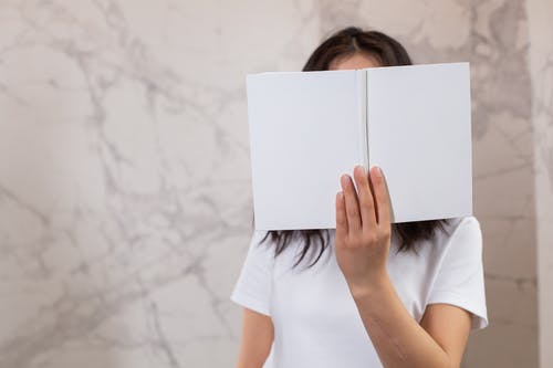 Unrecognizable female in casual t shirt with opened white mock up notebook in hands standing in light room near wall