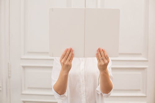 Anonymous woman with opened blank book