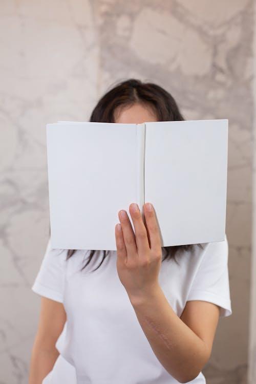 Wanita Dengan Kaos Putih Memegang Kertas Putih