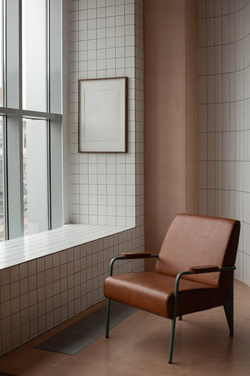 Blank frame hanging on tiled wall near window in small light room with soft brown leather armchair on floor at home