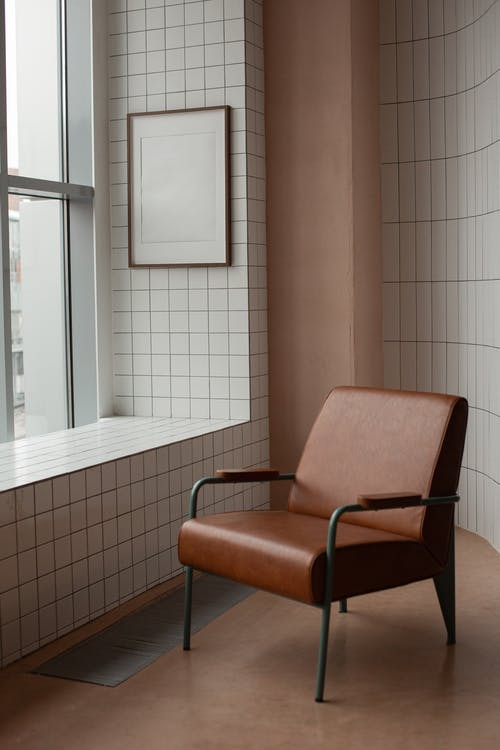 Comfortable brown armchair placed near tiled wall with mock up frame hanging near window in light small room at home