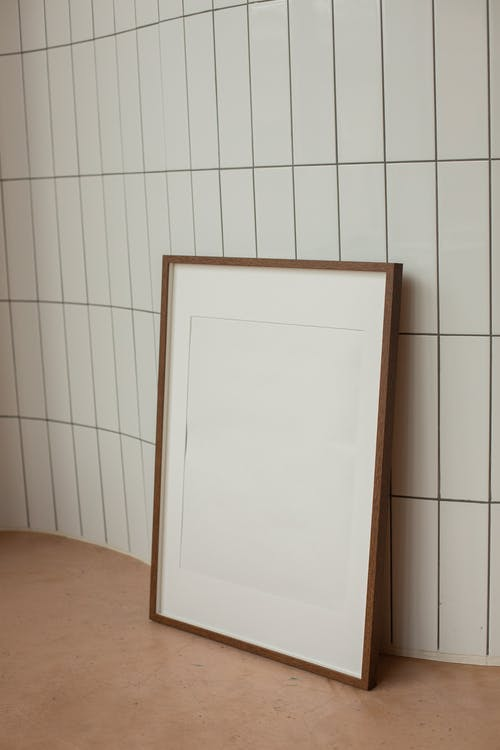 Blank rectangular shaped frame with brown border placed on floor near wall with white tiles in light room at home