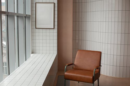 Brown armchair placed near mock up frame hanging near window and windowsill in small room with tiled walls at home