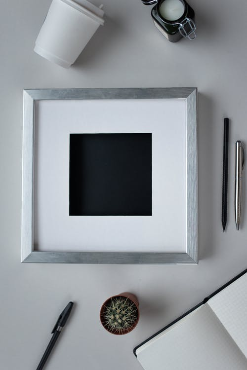 Top view arrangement of empty photo frame placed on white table near opened notebook pens and potted cactus