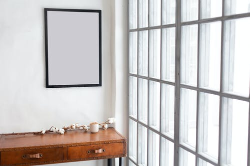 Interior of simple room with empty frame near rectangular shaped windows in daytime