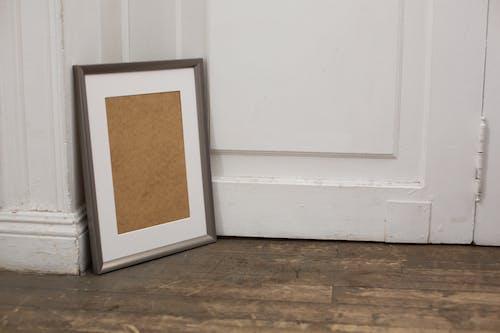 Empty carton frame placed on wooden floor near door