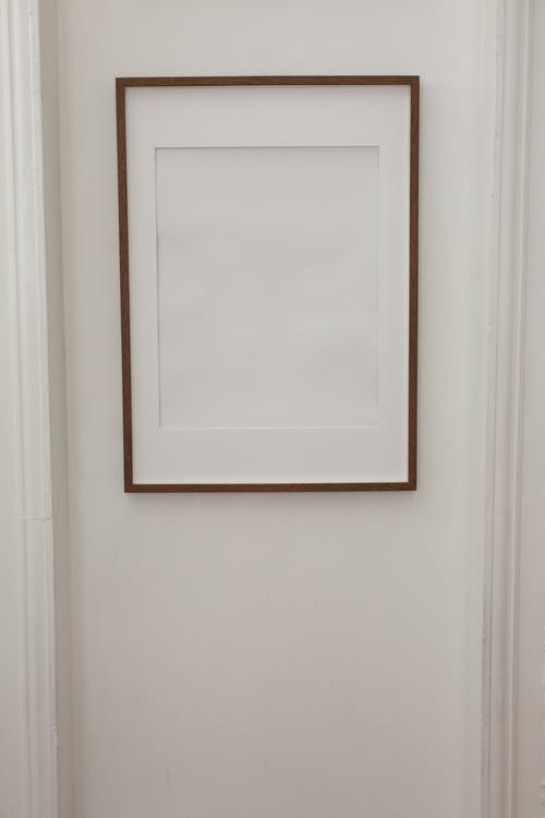 White minimal empty frame hanging on wall of contemporary flat with simple walls