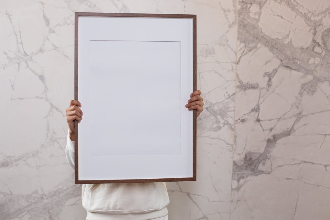 Crop anonymous person demonstrating white empty frame in hands near gray wall with patterns