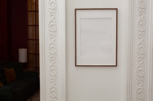Empty white frame hanging on wall with patterns