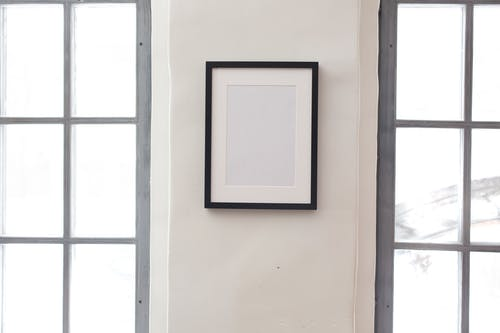 Interior of simple apartment with blank frame on white wall between rectangular shaped windows