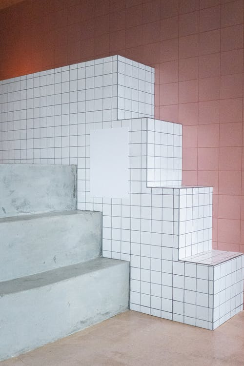 Empty white paint placed on decorative wall in form of stairs in light room with minimalistic design