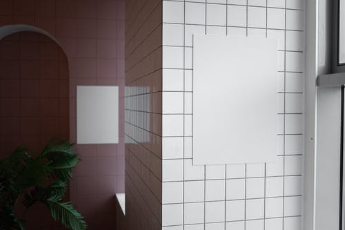 Interior of modern spacious room with empty canvases and tile walls in daytime