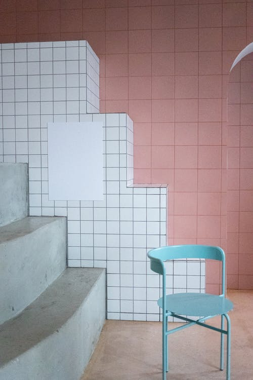 Interior of modern room with minimalistic metal chair and empty white canvas hanging on geometric tile walls
