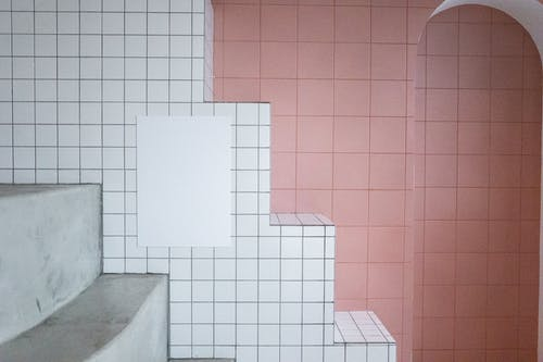 White blank paint hanging on tile white wall near arched entrance in room with minimalistic design