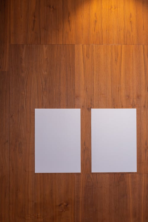 From above of empty white placards placed on wooden floor in room in daytime