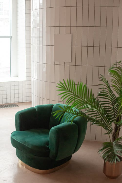 Empty light room with green armchair near potted plant and white canvas placed on tile wall near window