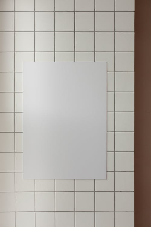 Bright empty room interior with white blank canvas placed on white tile wall