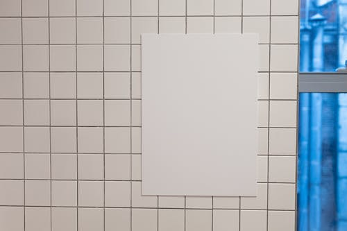 Blank white placard hanging on wall covered with white tiles inside of building