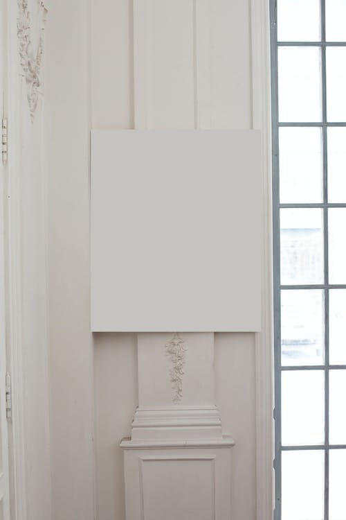 Blank white frame hanging at corner on wall with post and classic decorative elements near big window in light room