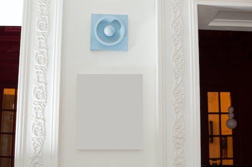 Blank frame hanging between decorated doorways