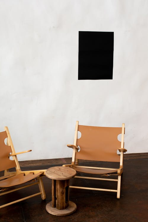 Wooden armchairs placed near white wall with creative mock up black paper with copy space in light room of modern studio