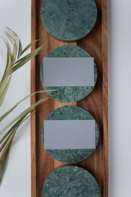 Top view of gray mock up business cards on round coasters in wooden tray on white table with green leaves