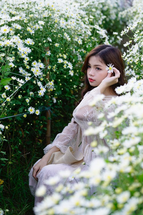 Contemplative ethnic teen with blooming chamomile in countryside
