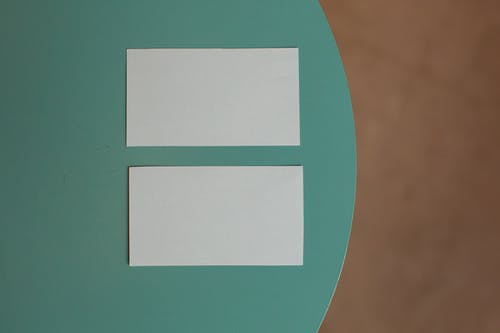 Top view of creative white mock up business cards with copy space placed on round green table in light room