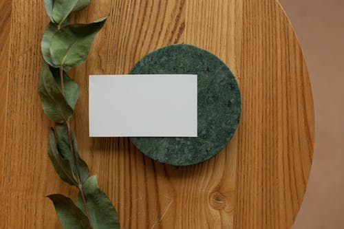 Top view of white mock up business card on round board placed on wooden table with green branch in room