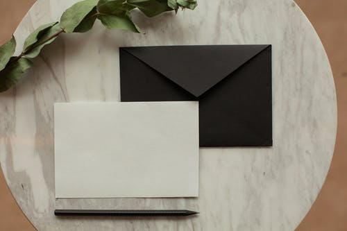 Top view of blank black envelope with white card placed on table with pencil and dry green sprig in modern room