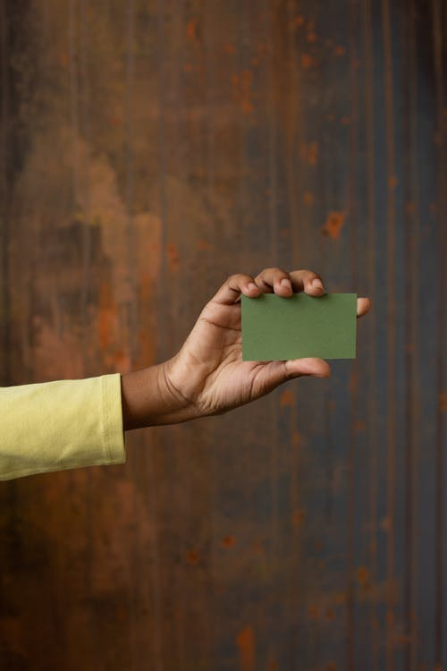 Anonymous African American person showing green blank business card with copy space in hand while standing near wooden wall in studio