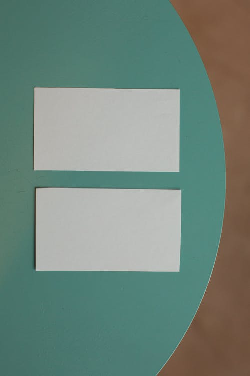 Top view of creative white mock up business cards placed on round green table in light room of modern studio