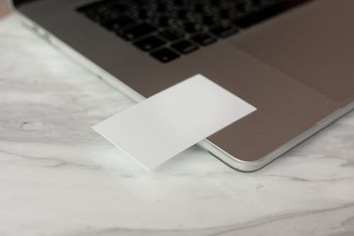 White mock up business cards with copy space placed on modern opened gray netbook on marble table in creative workplace