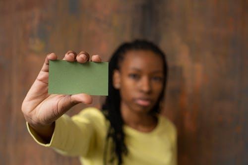 Wanita Dengan Kaos Leher Kru Kuning Memegang Kertas Kotak Hijau
