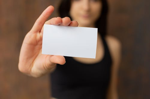 Crop woman showing blank business card