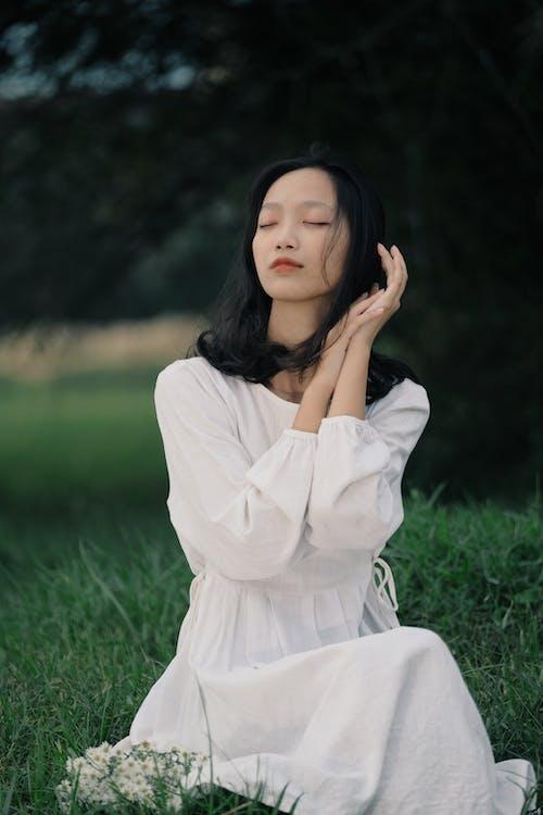 Dreamy Asian woman sitting on grassy lawn