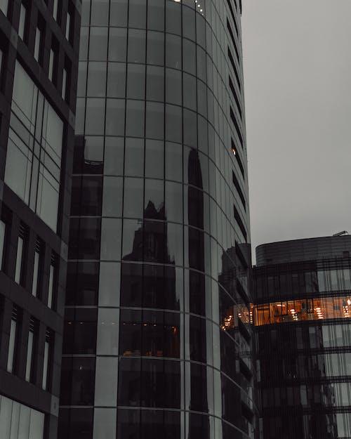 Modern skyscraper with glass walls under overcast sky