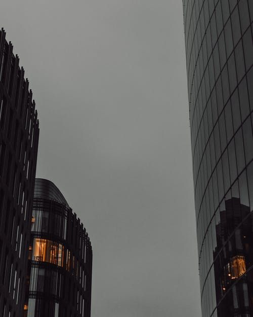 From below of contemporary skyscrapers located in city against cloudy sky in evening time