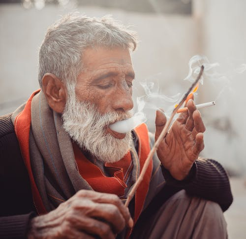 Old bearded ethnic male with wooden stick exhaling puffs of smoke while smoking cigarette on street