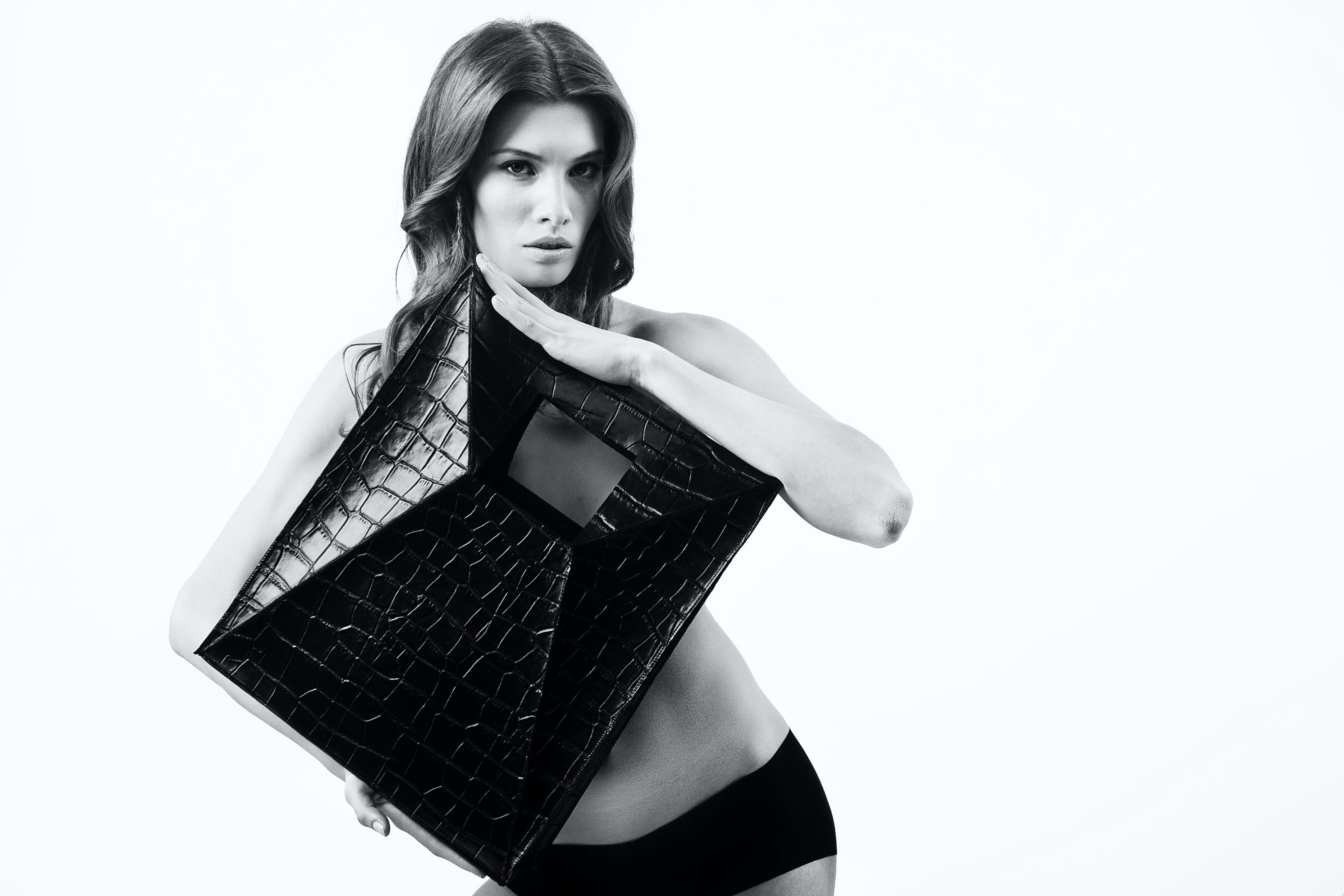 Greyscale Photography of Woman Holding Leather Square Covering Her Upper Body