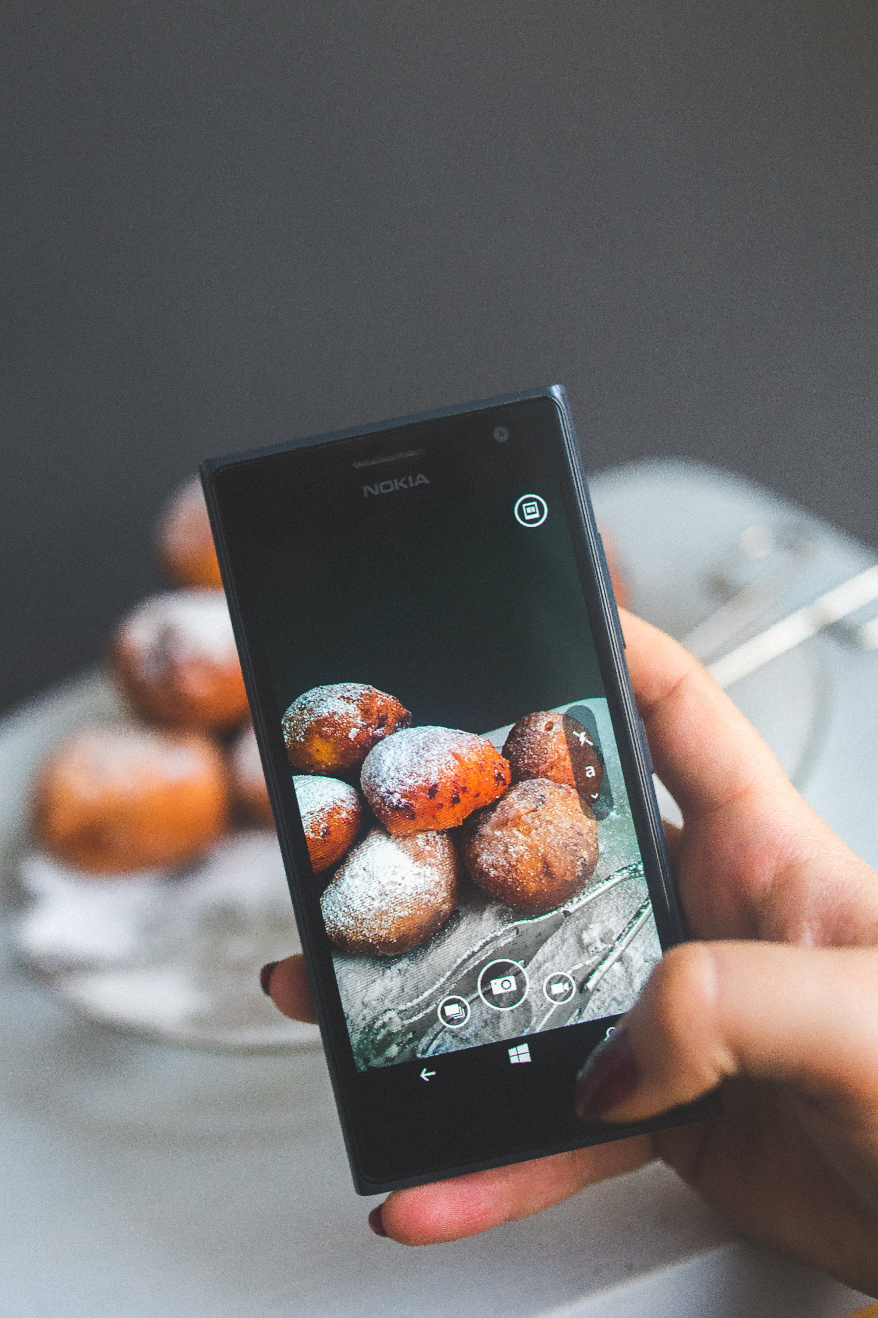 Woman hand taking picture of doughnuts
