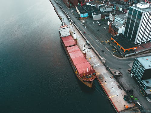 Drone view of modern dock with industrial ship moored in rippling water in daytime