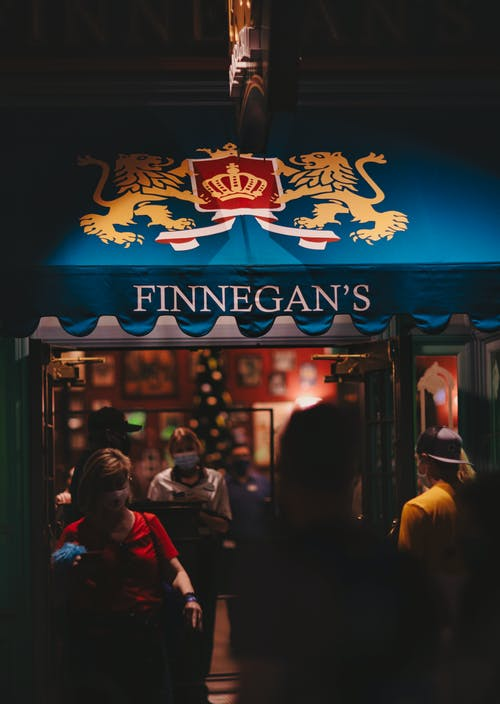 Crowded pub entrance with emblem on canopy