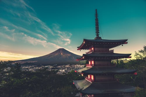Aged Asian church exterior against mount Fuji under blue cloudy sky on island of Honshu in Japan