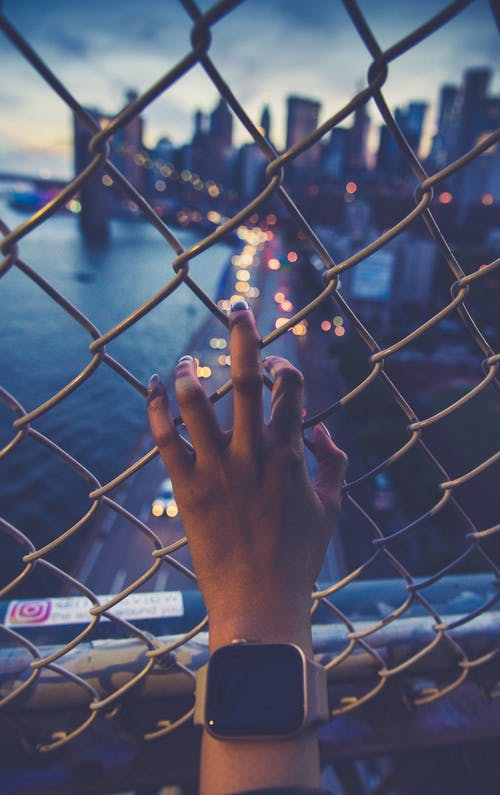 Crop anonymous female in wearable bracelet touching metal grid fence while admiring urban lake in modern town in evening
