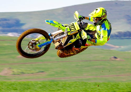 Man in Green and Yellow Motocross Suit Riding Motocross Dirt Bike