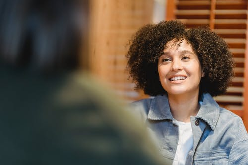 Cheerful young woman with Afro hairstyle talking with friend